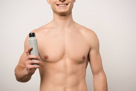 cropped view of smiling shirtless man holding deodorant isolated on grey
