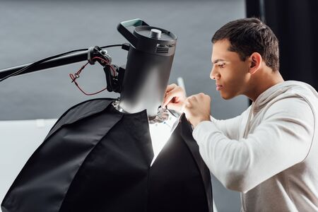 side view of handsome man looking at reflector in photo studio Imagens