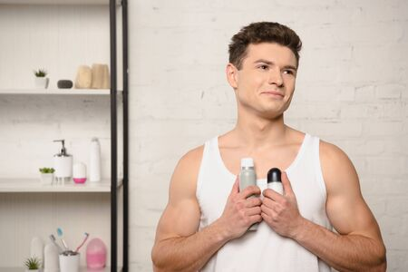 smiling young man in white sleeveless shirt looking away while holding deodorants Stock Photo