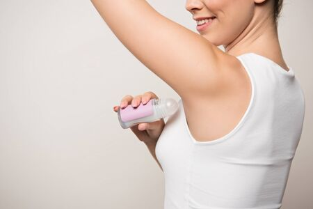 cropped view of smiling woman applying deodorant on underarm isolated on grey