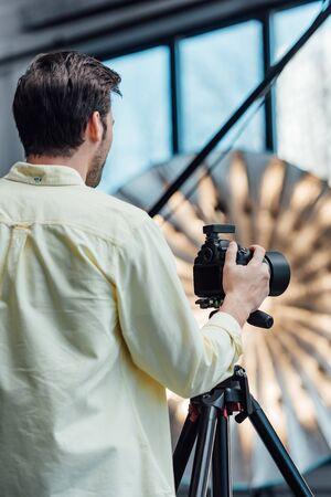 back view of photographer touching digital camera on tripod