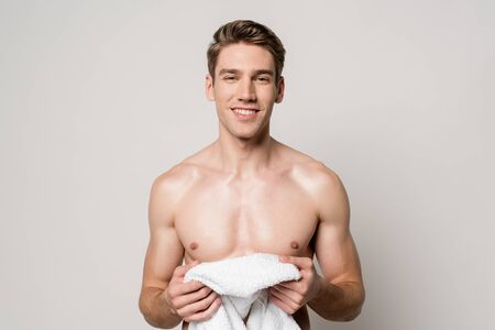 smiling sexy young naked man holding cotton towel isolated on grey