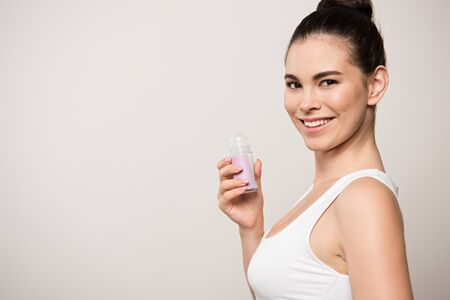 cheerful woman smiling at camera while holding deodorant isolated on grey