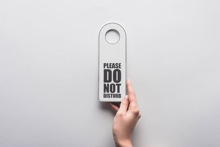 cropped view of woman holding please do no disturb sign on white background