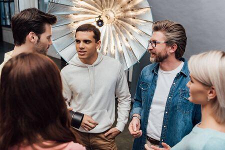 selective focus of men speaking near women in photo studio