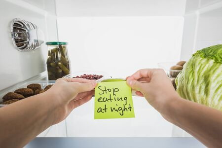 Cropped view of woman holding card with stop eating at night lettering with food in fridge isolated on white 写真素材