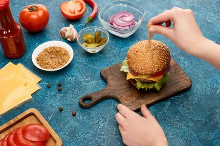 partial view of woman cooking delicious burger on blue textured surface
