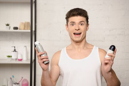 excited young man in white sleeveless shirt looking at camera while holding deodorants