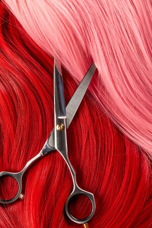 Top view of scissors on colored pink and red hair