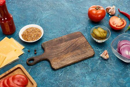 fresh burger ingredients around wooden cutting board on blue textured surface