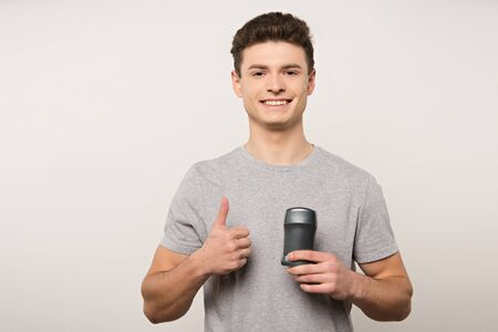 smiling man in grey t-shirt holding deodorant and showing thumb up isolated on grey Stock Photo
