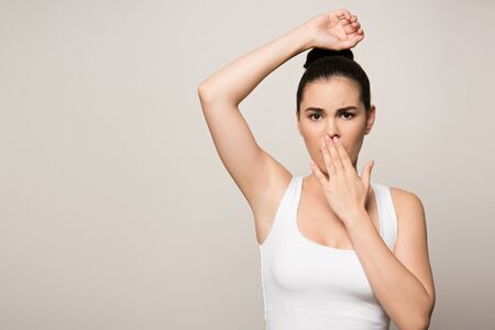 shocked woman covering mouth with hand while looking at camera isolated on grey