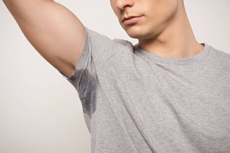 cropped view of young man in grey t-shirt with sweaty underarm isolated on grey Stockfoto
