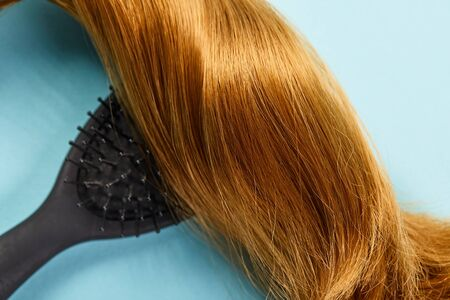 Top view of shiny brown hair and hairbrush on blue background