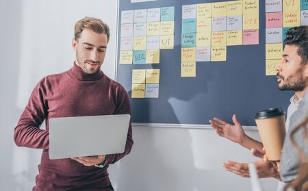 mixed race man talking with scrum master using laptop Stock Photo
