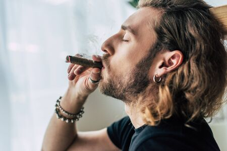 side view of fashionable casual businessman in total black outfit smoking cigar with closed eyes in office Zdjęcie Seryjne