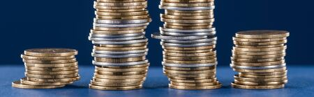 stacks of metal silver and golden coins on blue background, panoramic shot