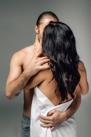 passionate nude couple hugging and kissing in sheets, isolated on grey Banque d'images