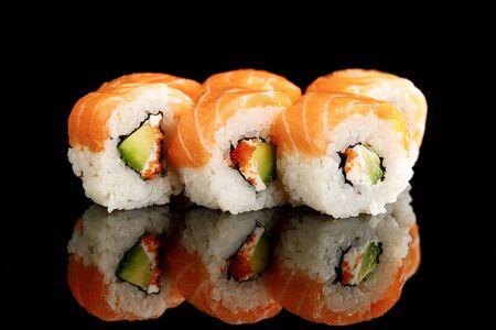 Sushi fresco e delizioso di Philadelphia con avocado, formaggio cremoso, salmone e caviale di masago isolato su nero con riflesso