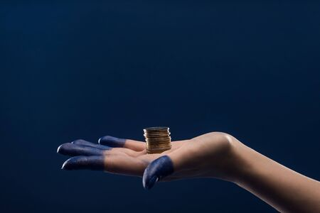 cropped view of female hand with painted fingers holding coins isolated on blue