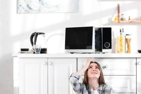 sad and attractive woman looking at broken microwave in kitchen
