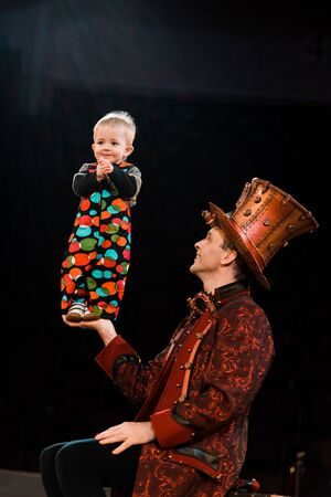 happy man holding cute acrobatic toddler in hand