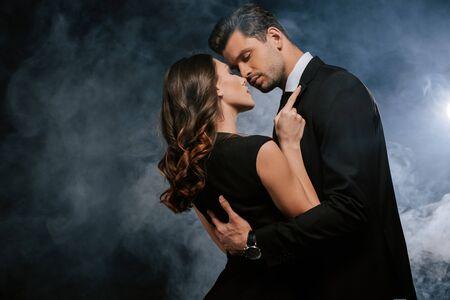 donna attraente che abbraccia bell'uomo su nero con fumo