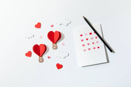top view of greeting card with hearts and pencil near paper heart shaped air balloons in clouds on white background Stock Photo
