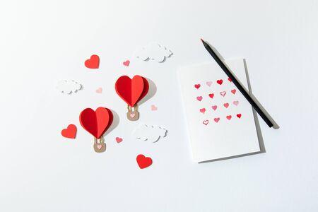 Vista superior de la tarjeta de felicitación con corazones y lápiz cerca de globos de aire en forma de corazón de papel en las nubes sobre fondo blanco. Foto de archivo