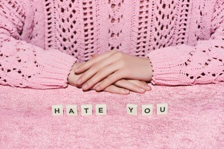 cropped view of woman in sweater near hate you lettering on pink velour cloth, girlish concept Imagens