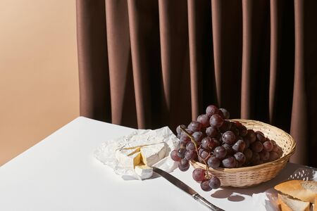 classic still life with grape in basket, brie cheese and baguette on table near curtain isolated on beige Reklamní fotografie