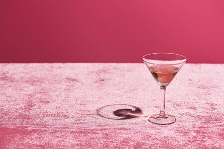 rose wine in glass on velour pink cloth isolated on pink, girlish concept