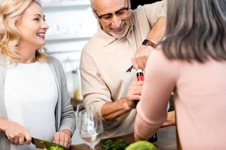 El enfoque selectivo del hombre abriendo la botella con vino y mujer cortando lechuga