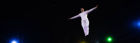 panoramic shot of handsome air acrobat with outstretched hands in arena of circus Banco de Imagens