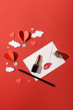 top view of paper clouds and heart shaped air balloons, envelope with lip print, lipstick and pencil on red background