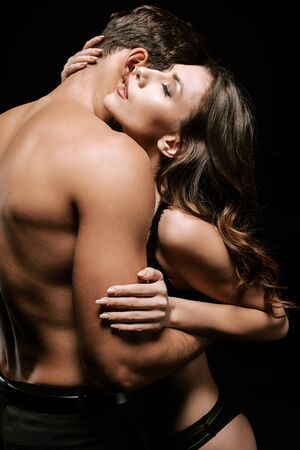 sexy girl with closed eyes hugging man isolated on black