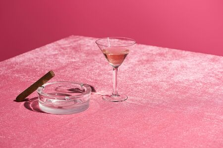 rose wine in glass near cigar on ashtray on velour pink cloth isolated on pink, girlish concept