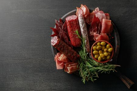 top view of delicious meat platter served with olives and herbs on wooden black table