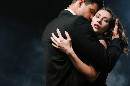 passionate man hugging sensual woman on black with smoke