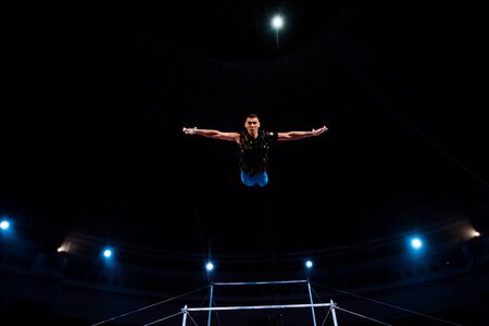 athletic gymnast with outstretched hands in arena of circus