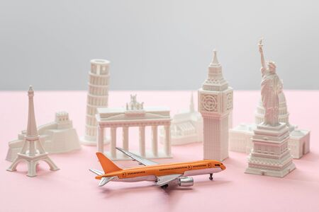 toy airplane near small statuettes of different countries on grey and pink 版權商用圖片