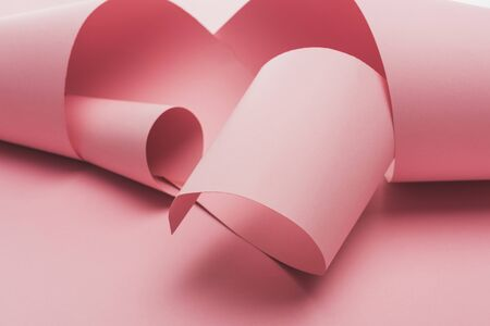 pink paper swirls with shadow on pink background