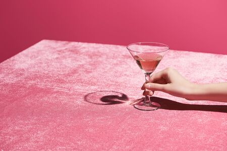 cropped view of woman holding glass of rose wine on velour cloth isolated on pink, girlish concept