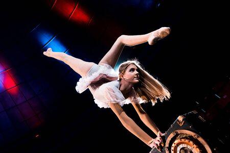 fille flexible faisant le poirier tout en jouant dans l'arène du cirque
