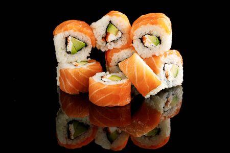 délicieux sushis de Philadelphie avec avocat, fromage crémeux, saumon et caviar de masago isolés sur fond noir avec reflet Banque d'images