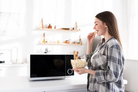side view of smiling and attractive woman eating popcorn near microwave