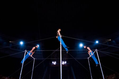 low angle view of gymnasts performing on horizontal bars in circus Banco de Imagens