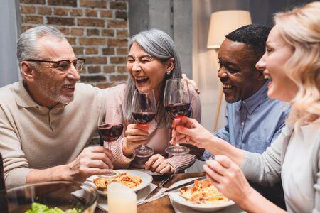 Amigos multiculturales sonrientes hablando y tintineando con copas de vino durante la cena