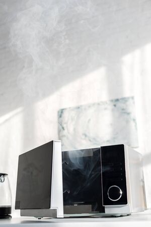 broken and steamy microwave on table in kitchen