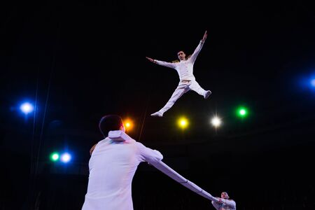 low angle view of handsome air acrobat with outstretched hands jumping near pole in arena of circus 스톡 콘텐츠